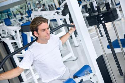 man at the gym doing exercises on a machine
