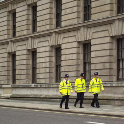 Three policemen walking on the side walk in London, England