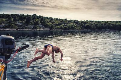 A man makes a header off aboard a sailing yacht