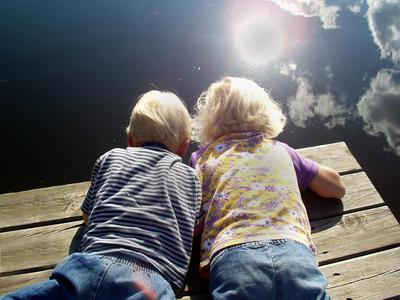 Children are looking into a lake